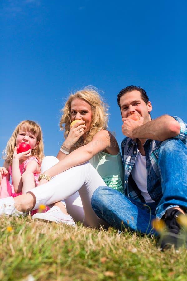 Ouders en dochter die appelen eten stock afbeeldingen