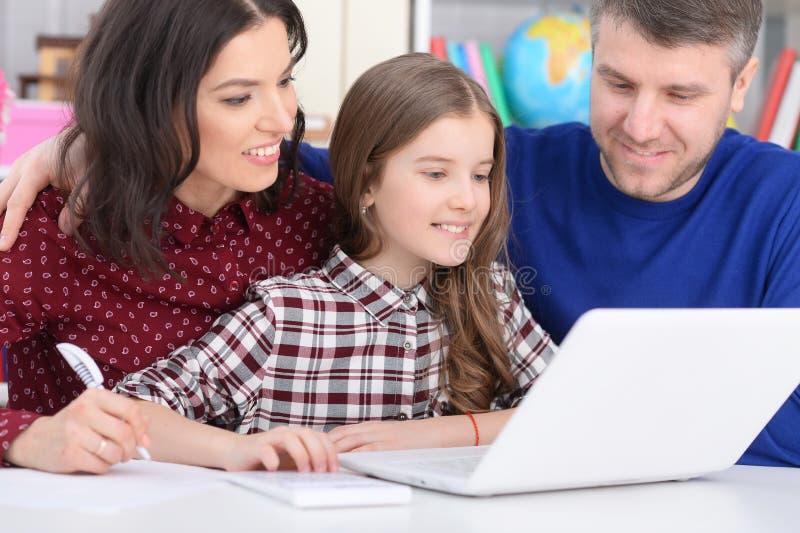 Ouders en dochter die laptop in ruimte met behulp van stock foto's