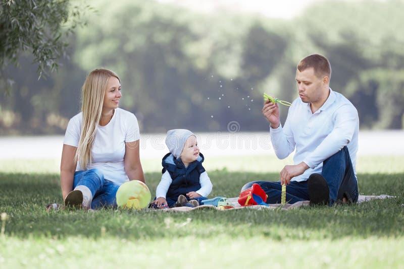 Ouders en hun kleine zoons blazende bellen op een gang van de de zomerdag stock afbeeldingen