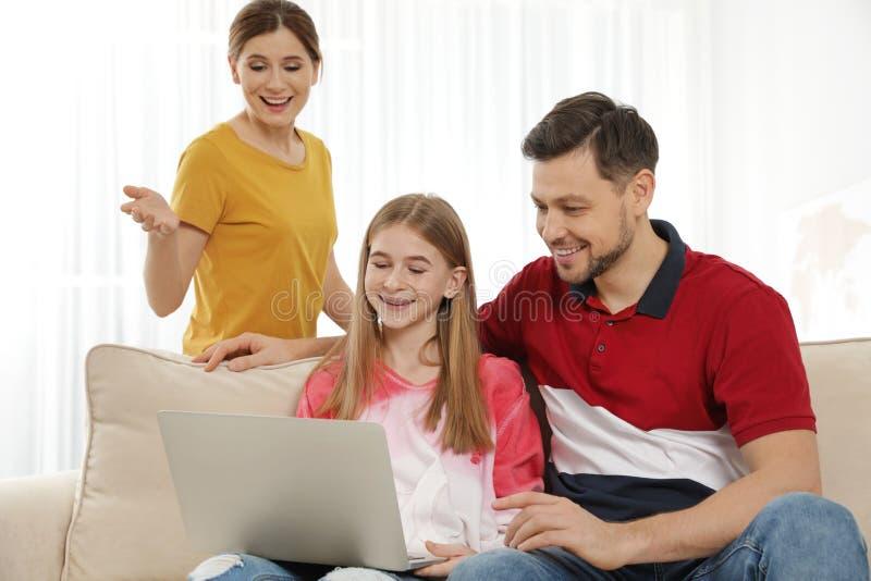 Ouders en hun tienerdochter met laptop computer stock afbeelding
