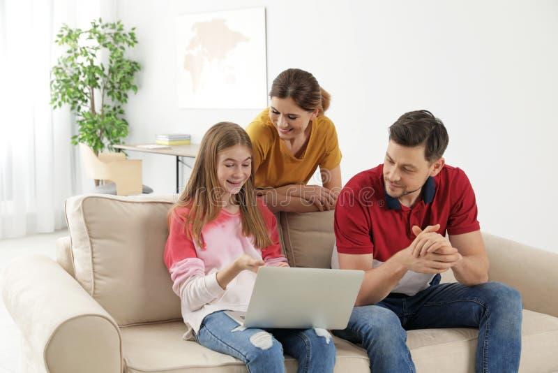 Ouders en hun tienerdochter met laptop computer stock foto