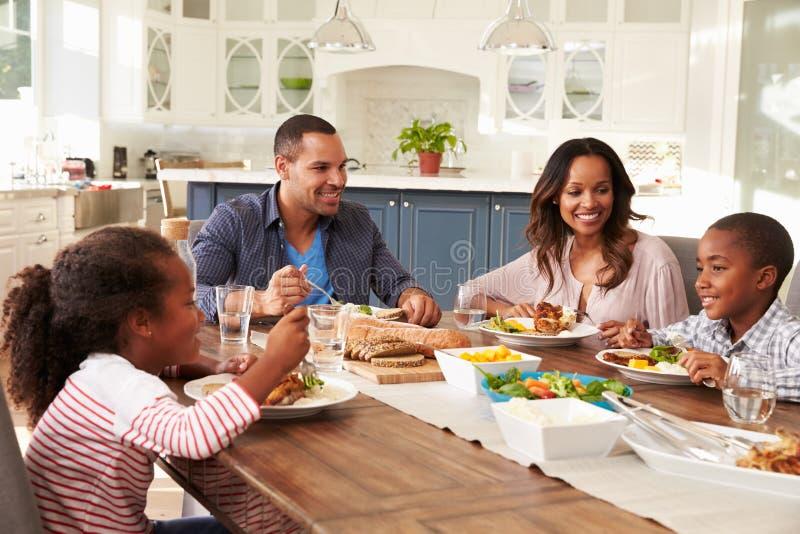 Ouders en hun twee kinderen die bij keukenlijst eten royalty-vrije stock foto