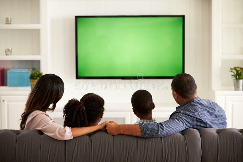 Ouders en hun twee kinderen die op TV samen thuis letten stock afbeeldingen