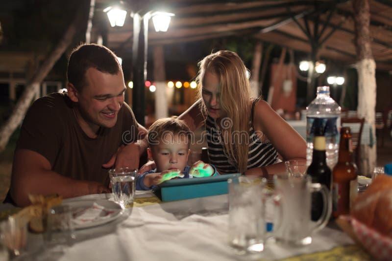 Ouders en kind met tabletpc in openluchtkoffie royalty-vrije stock afbeelding
