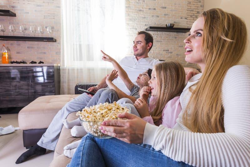 Ouders en kinderen die op TV letten stock foto's