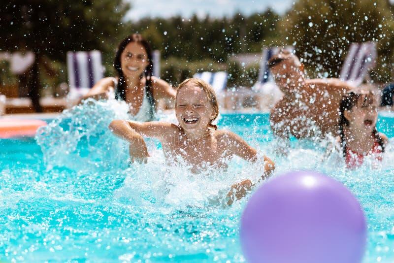 Ouders en kinderen die terwijl het spelen van bal in zwembad lachen royalty-vrije stock foto's