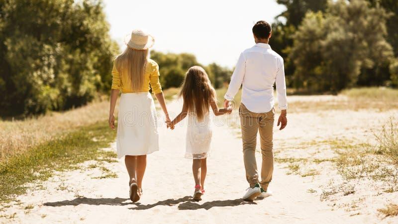 Ouders en meisje die in platteland lopen stock afbeelding