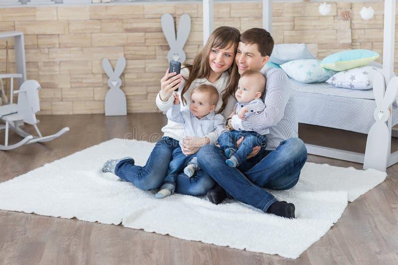 Ouders en tweelingen die selfie door smartphone nemen stock afbeeldingen