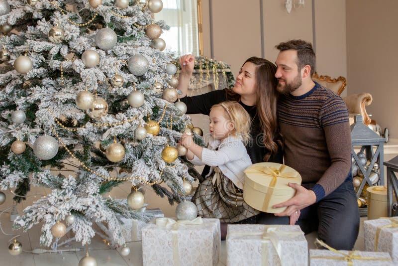 Ouders en zijn kleine dochter die Kerstboom met speelgoed en slingers verfraaien stock foto