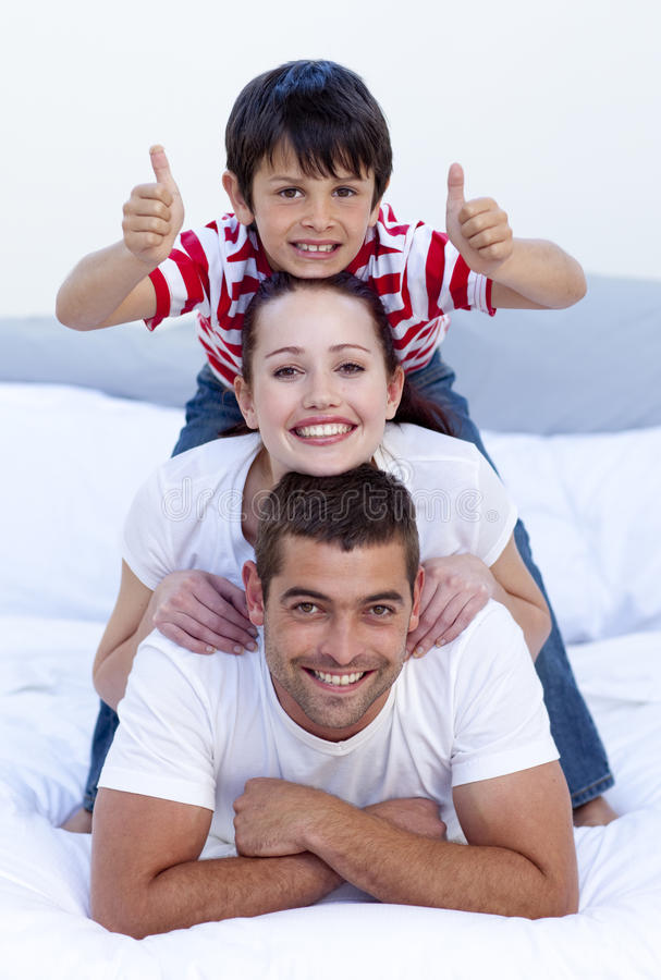 Ouders en zoon in bed met omhoog duimen royalty-vrije stock foto