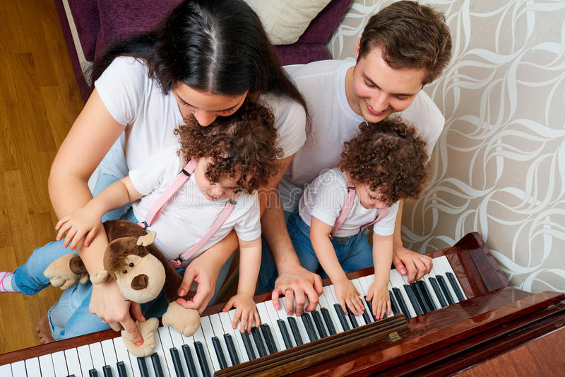 Ouders met de studiemuziek van dochterstweelingen bij de piano Hoogste mening royalty-vrije stock afbeeldingen