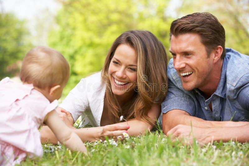 Ouders met de Zitting van het Meisje van de Baby op Gebied royalty-vrije stock foto