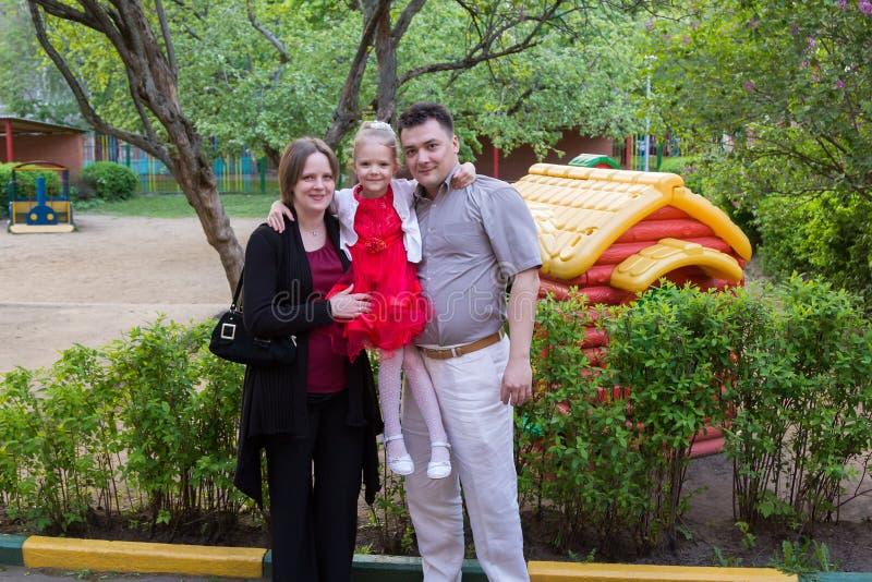 Ouders met hun dochter in de speelplaats in tuin stock foto's