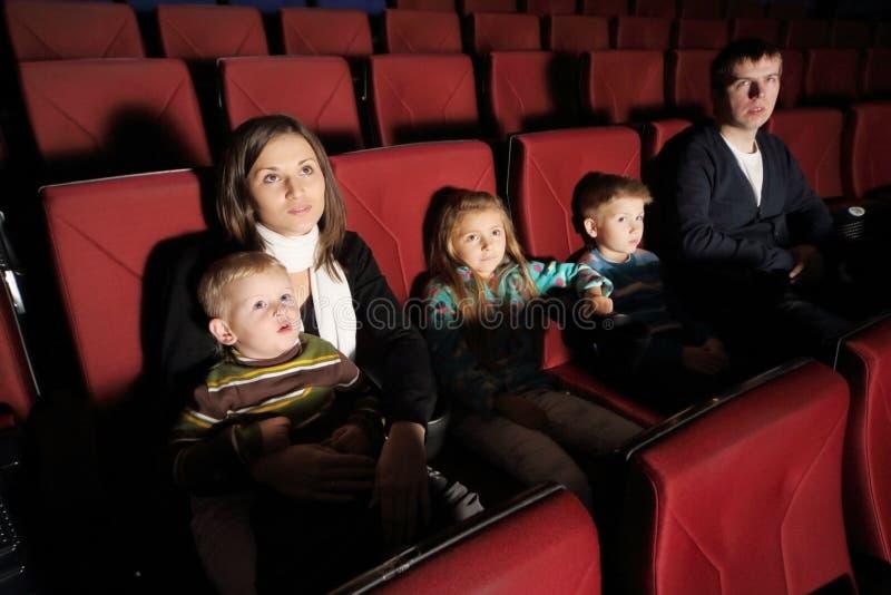 Ouders met hun kinderen die op een film letten stock foto's