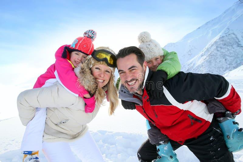 Ouders met hun kinderen op hun ruggen die in de sneeuw spelen stock fotografie