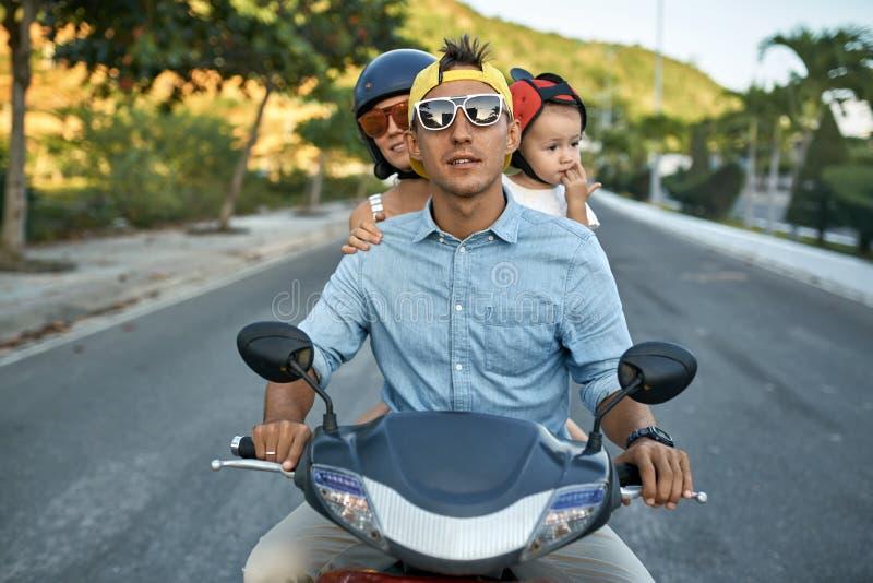 Ouders met hun kleine jong geitje berijdende motorfiets op zonnige stadsstraat royalty-vrije stock afbeelding
