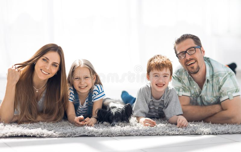 Ouders met kinderen die in de woonkamer op het tapijt liggen stock afbeelding
