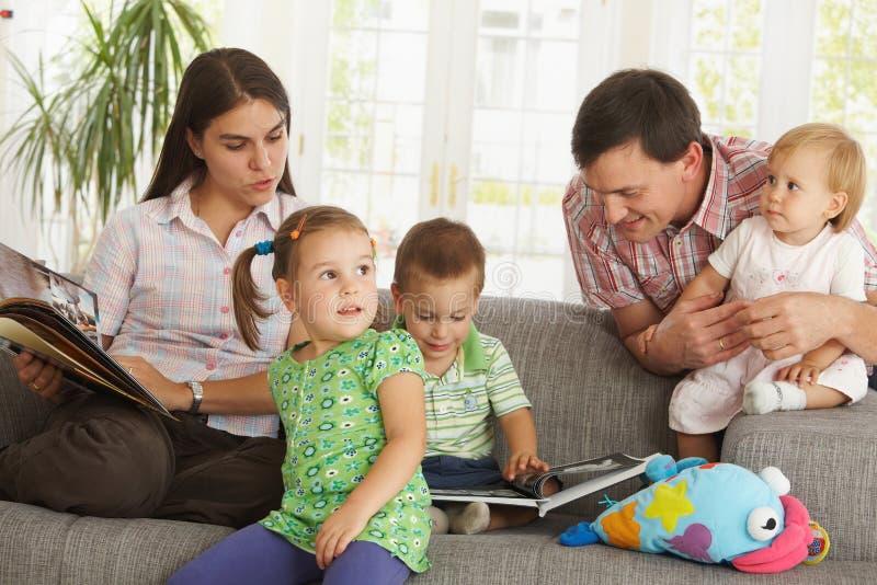 Ouders met kinderen thuis stock afbeelding