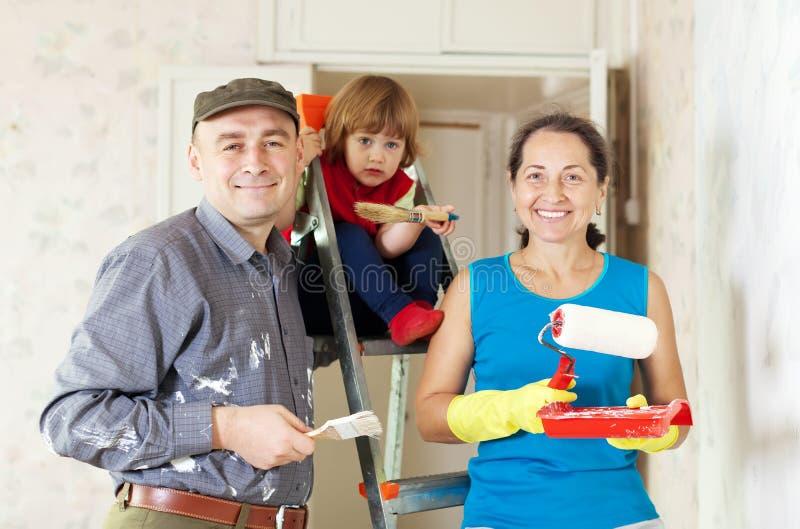 Ouders met kindreparaties thuis royalty-vrije stock afbeeldingen