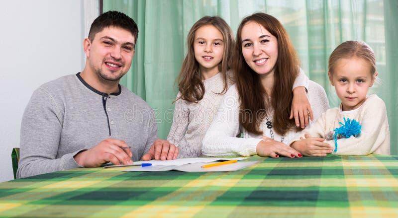 Ouders met kleine kinderen die verzekering en het glimlachen kopen stock afbeelding