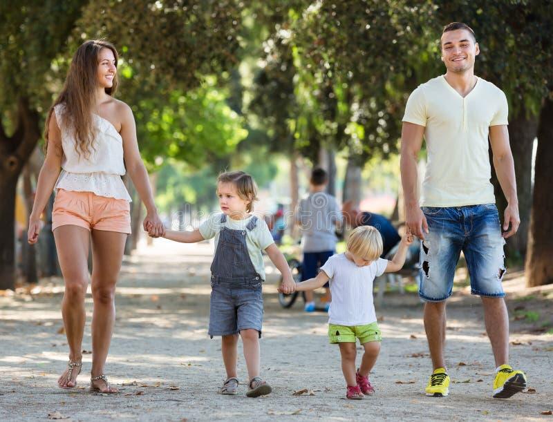 Ouders met twee kleine kinderen door park royalty-vrije stock fotografie