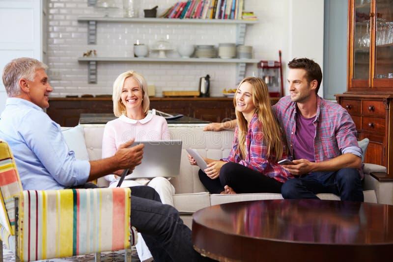 Ouders met Volwassen Nakomelingen die Digitale Apparaten thuis met behulp van royalty-vrije stock foto's