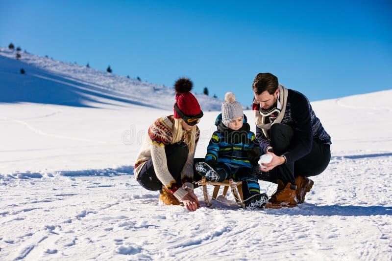 Ouderschap, manier, seizoen en mensenconcept - gelukkige familie met kind die op slee in de winter in openlucht lopen stock fotografie