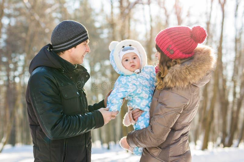 Ouderschap, seizoen en mensenconcept - gelukkige familie met kind in de winterkleren in openlucht royalty-vrije stock foto's
