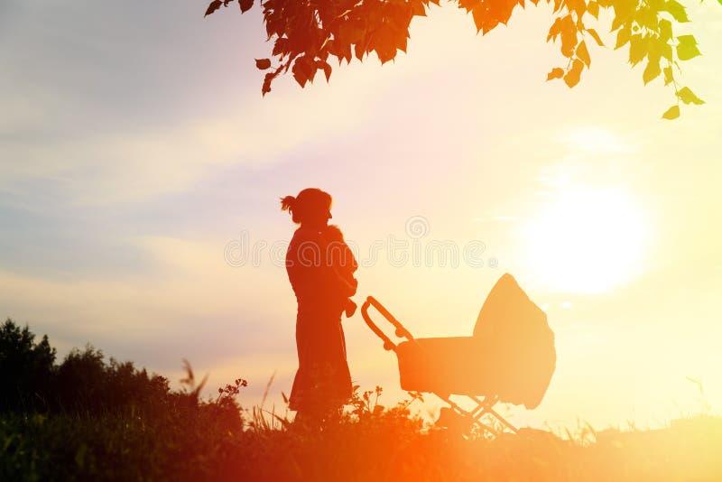 Ouderschapconcept - silhouet van moeder met weinig baby in aard stock afbeelding