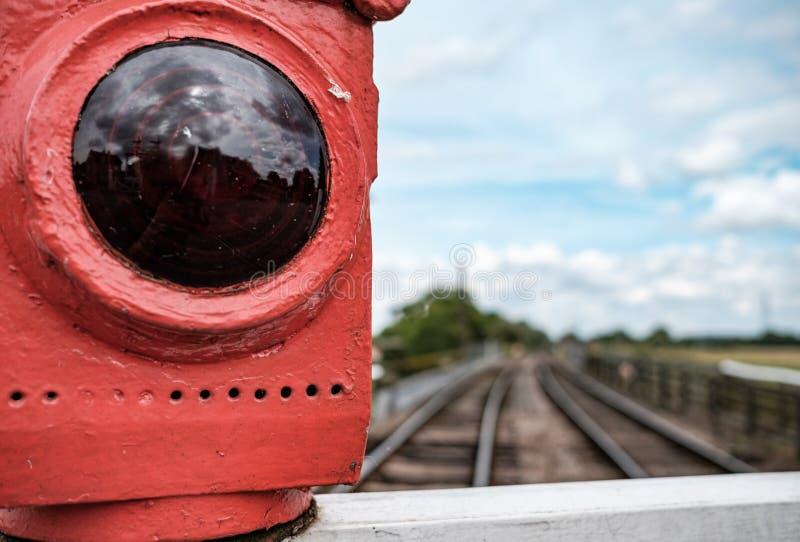 Ouderwets, gas aangestoken rood gezien waarschuwingslicht in bijlage aan een spoorwegovergang stock afbeelding