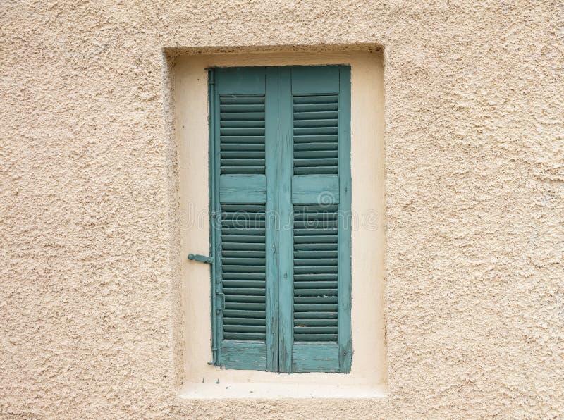 Ouderwets versleten venster met groene houten die blinden, op gepleisterde muurachtergrond worden gesloten stock foto's