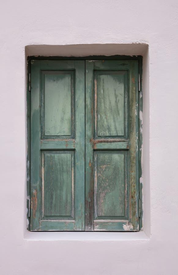Ouderwets versleten venster met groene houten die blinden, op geschilderde muurachtergrond worden gesloten stock foto