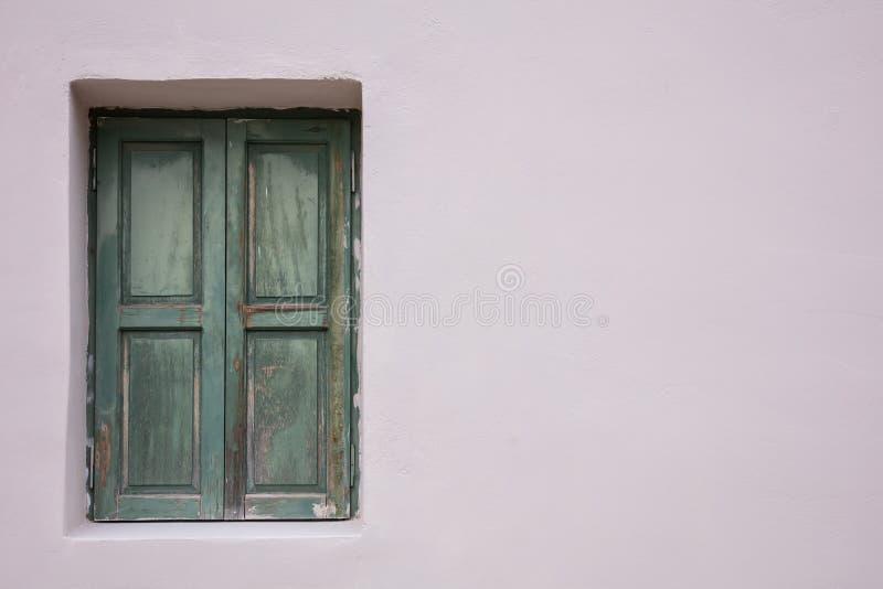 Ouderwets versleten venster met groene houten die blinden, op geschilderde muurachtergrond worden gesloten royalty-vrije stock afbeeldingen