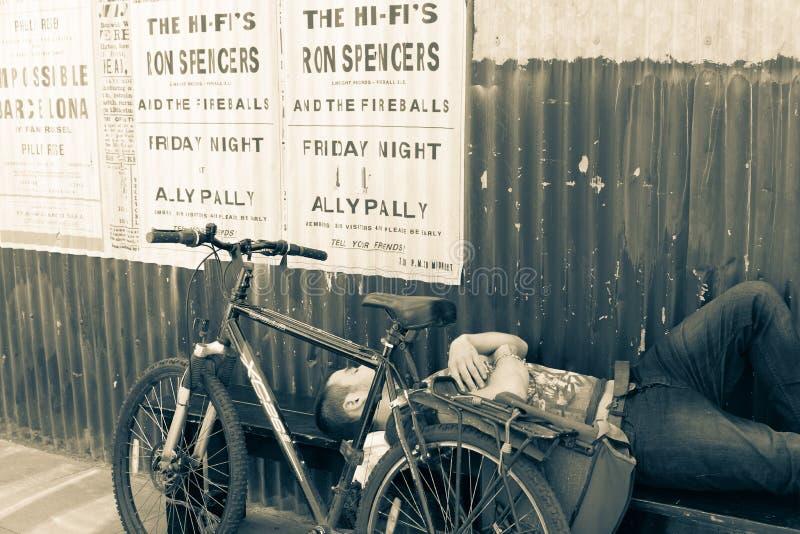 Ouderwetse affiches voor show in Ally Pally op golfijzermuur boven een in slaap mens royalty-vrije stock fotografie