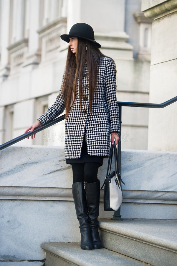 Oudoors элегантной и модной молодой коммерсантки стоящие держа шляпу сумки нося стоковая фотография