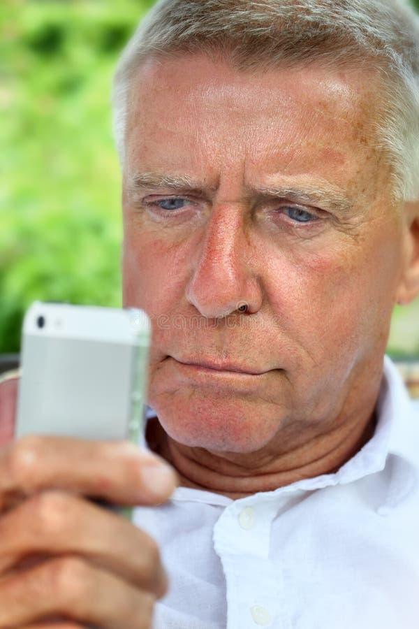 Oudste die op een slimme telefoon doorbladeren royalty-vrije stock foto's