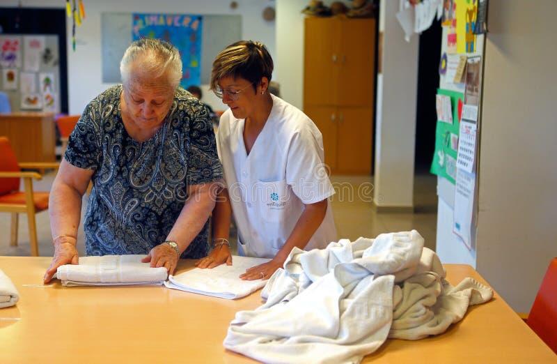 Oudste en verpleegster bij de wasserijdagelijkse werken op een verpleeghuis in Mallorca royalty-vrije stock foto's