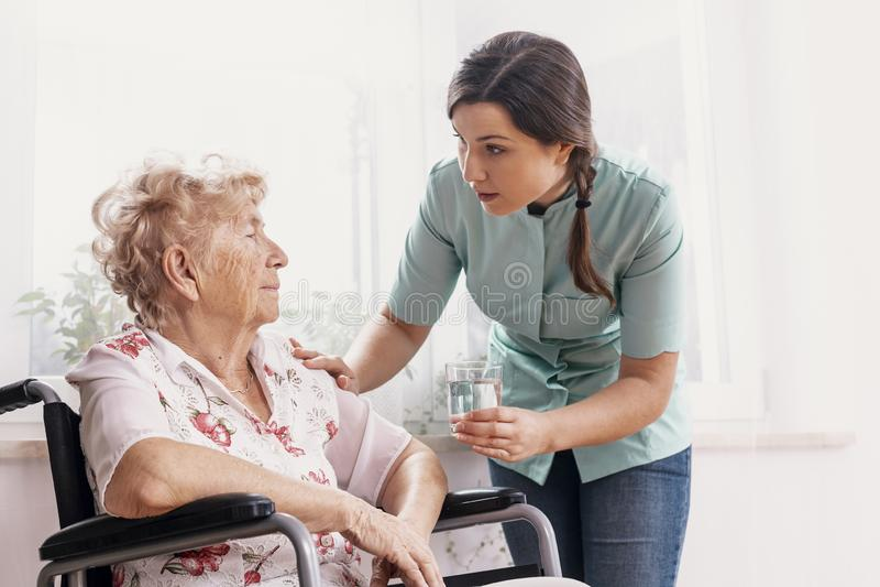 Oudste op rolstoel, ondersteunende verpleegster die haar glas water geven stock foto's