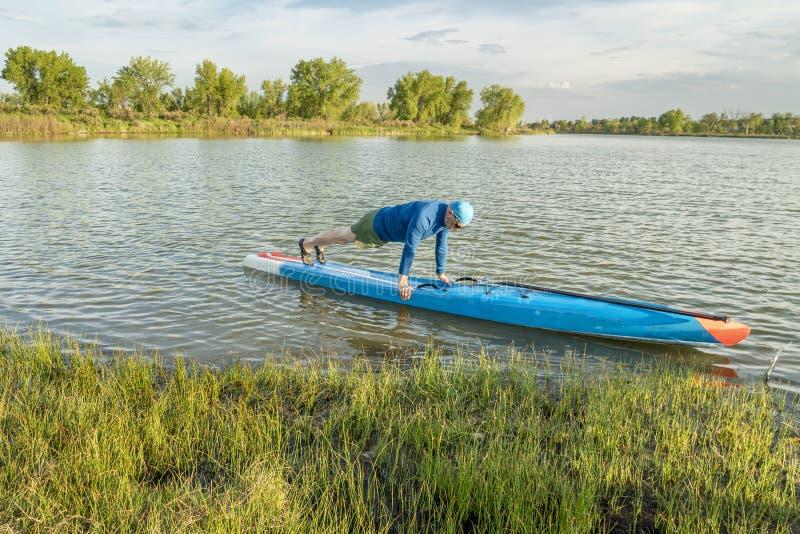 Oudste paddler op tribune omhoog paddleboard royalty-vrije stock afbeelding