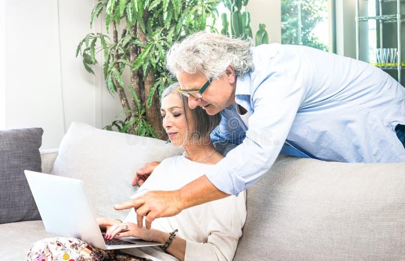 Oudste teruggetrokken paar die laptop computer thuis op bank met behulp van - Gr stock afbeelding