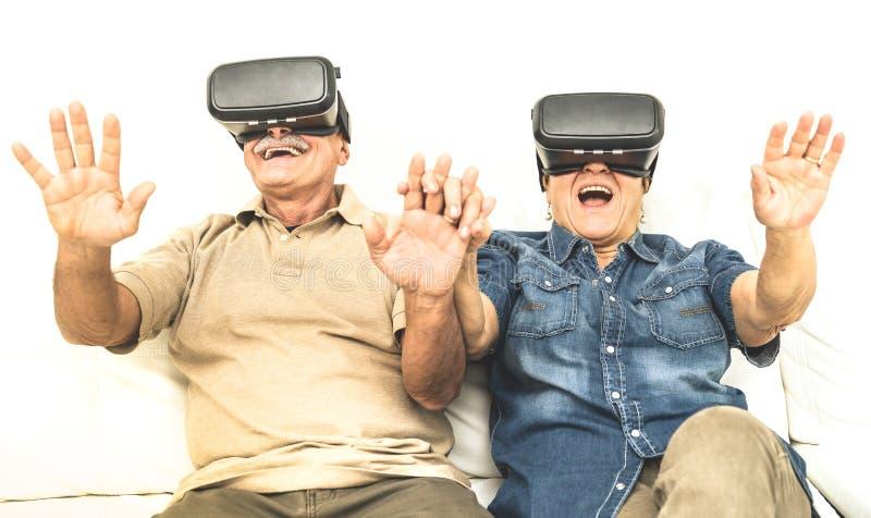 Oudste teruggetrokken paar die pret samen met virtuele werkelijkheidsglazen hebben stock afbeeldingen