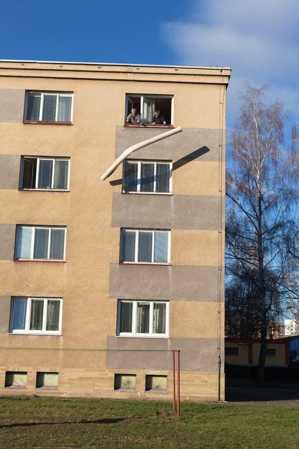 Oudsten die gerold tapijt werpen uit een venster van een gebouw stock foto