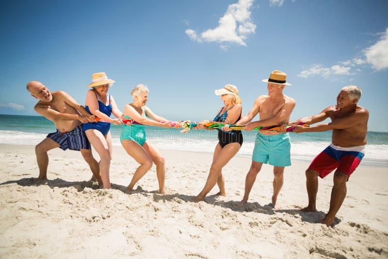 Oudsten die touwtrekwedstrijd spelen bij het strand royalty-vrije stock foto's