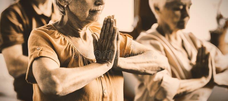 Oudsten die yoga met gesloten ogen doen stock foto