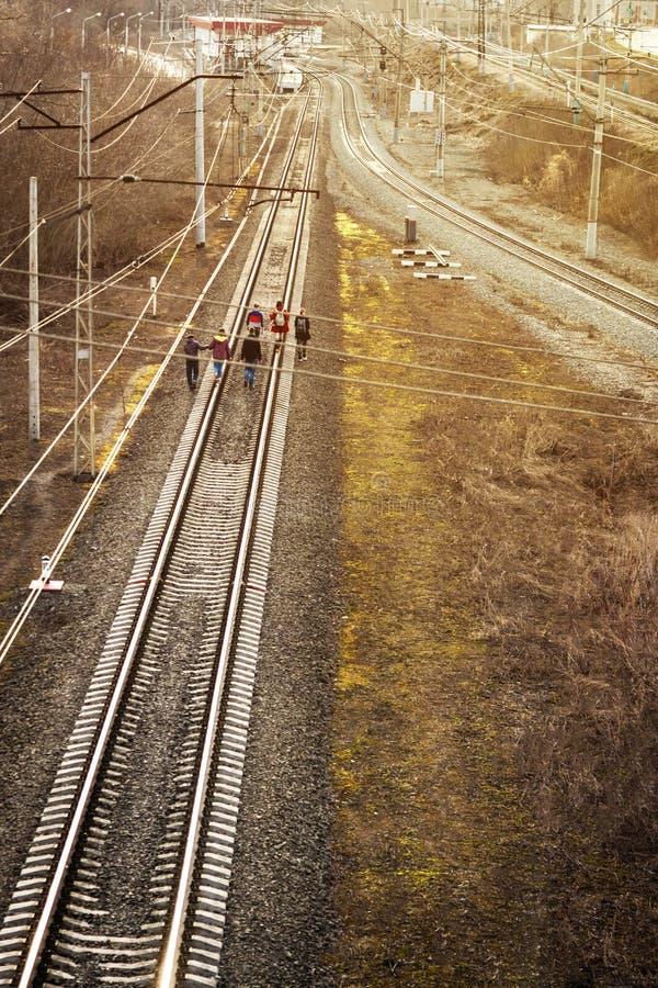 Oufa, Russie - 7 avril 2019 : le groupe d'adolescents vont sur des rails vers le coucher de soleil, les voies de train photographie stock