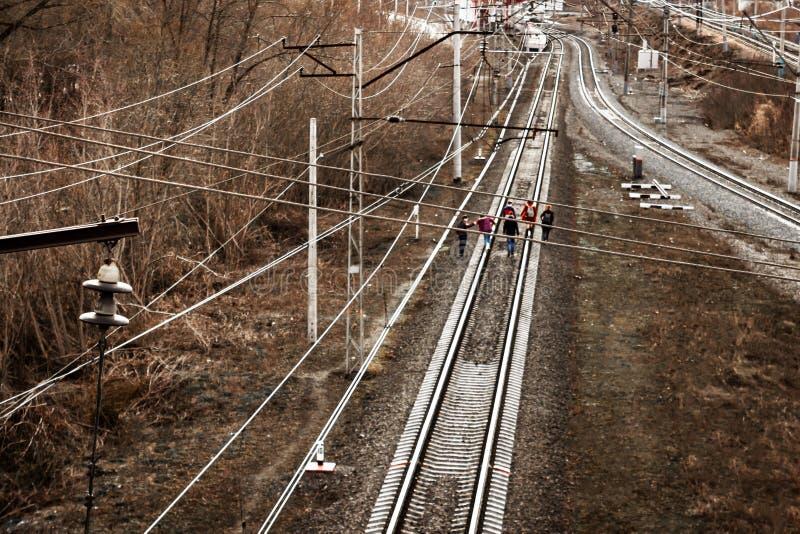 Oufa, Russie - 7 avril 2019 : un groupe d'adolescents ou les ?coliers vont sur les voies de train, les rayons du coucher de solei images libres de droits