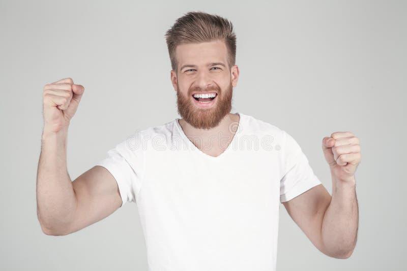 Oui gagnant Le jeune homme gai sont repr?sentant et faisant des gestes la victoire sur le fond pur dans l'?quipement occasionnel  photo stock
