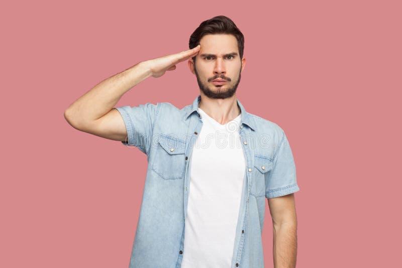 Oui monsieur Portrait de jeune homme barbu beau sérieux la position bleue de chemise de style occasionnel avec le salut et en reg image stock