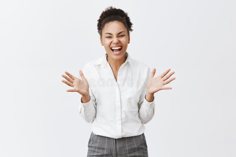 Oui nous avons obtenu l'affaire Femme à la peau foncée insouciante et optimiste belle dans la chemise et le pantalon, faisant des photos libres de droits