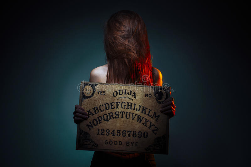 OUIJA deska dla wróżby Dziewczyna trzyma OUIJA deskę Kobieta z długim czerwonym włosianym Halloween Tajemnicza wróżby rozmowa zdjęcia royalty free